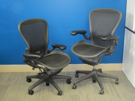 Two Herman Miller Aeron Chairs, coloured black, tilted toward each other in front of a blue wall.