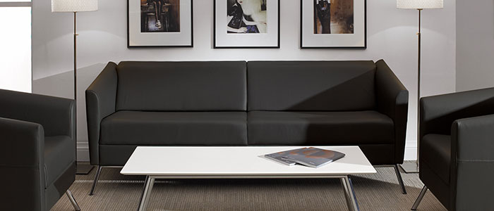 An assortment of charcoal grey seating from the Global Furniture Wind series grouped around a rectangular coffee table in an office with white walls and walnut-coloured flooring.