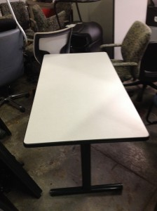 A white 36x60 folding table with a white top, rounded black trim, and heavy black legs at either end.