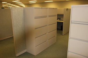 Two 5-drawer lateral cabinets standing side by side against a cubicle wall in an office space.