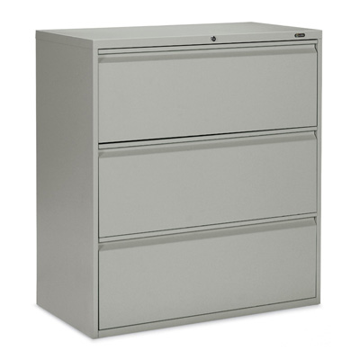 A grey 3-drawer metal file cabinet turned slightly to the left of the camera against a black background.