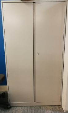 A tall, beige steelcase universal storage unit resting against a blue wall.