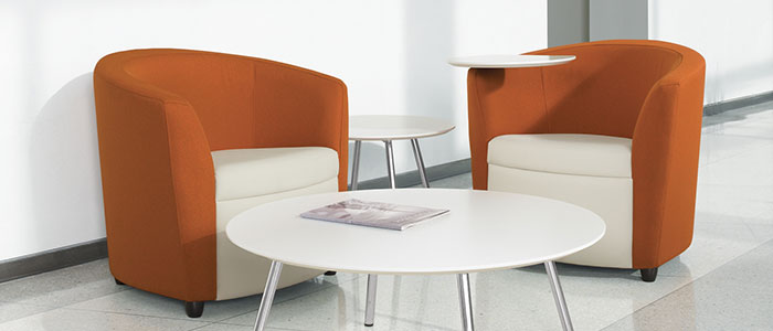 Two of the best leather club chairs from Sirena, featuring white seats and orange leather trim. Centered around a low circular coffee table.