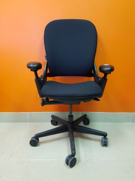 A navy blue Steelcase Leap Chair (V1) captured at the front against an orange wall.