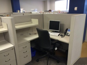 Beige call center cubicles joined together in an office space, one of them lightly furnished with a monitor and a desk chair.