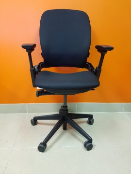 A dark navy blue Steelcase Leap Chair V2 pointing straight toward the camera, standing in front of an orange wall.