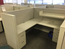 Beige and white used steelcase cubicles joined together in an office with dimmed lighting from the windows on the wall several meters behind them.