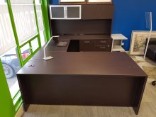 A dark brown U-shaped corner desk with a high storage shelf attached on the right, facing the window.