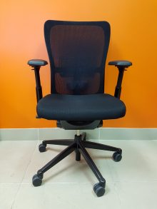 A black Haworth Zody Chair, facing the front against an orange wall.