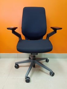 A black Steelcase Gesture Chair with armrests pictured from the front, against an orange wall.