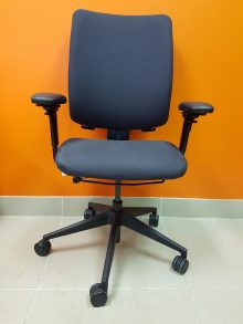 A Steelcase Crew Chair, charcoal colour, captured straight on against an orange wall.
