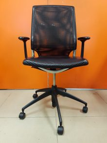 A black Vitra Meda Chair with a mesh back, in black, facing forward in front of an orange wall.