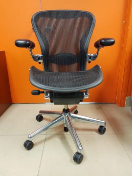 A black mesh Herman Miller aeron chair, fully loaded with chome facing the camera straight.