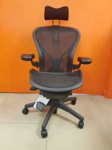 Herman Miller Aeron chair with a head support pad attached, captured straight on against an orange wall.