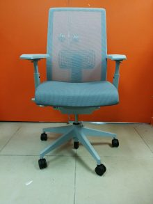 A grey Haworth Very Conference Chair with a mesh back facing the camera in front of an orange wall.