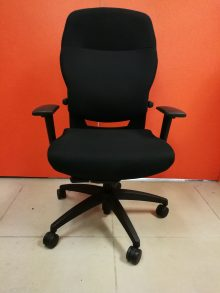A black Teknion Savera Chair, padded on the seat and the back with armrests, angled toward the camera.