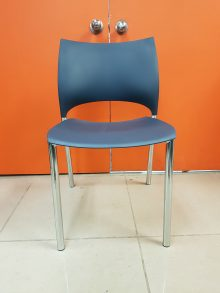 Keilhauer Loon side stacking chair in dark grey-blue plastic with four metal legs, facing straight toward the camera.