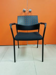 A black Sonic padded stacking chair with arms and a plastic ventilated back and four legs, facing straight toward the camera.