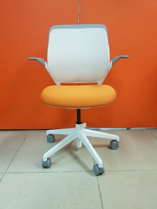 A Steelcase Cobi Chair with an orange seat, a white back, and grey edges on the armrests and the top of the back. Pictured straight on against a dark orange wall.