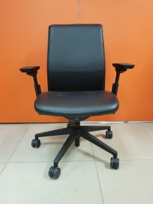 A black leather Steelcase Think Office Chair against an orange wall, captured head-on.