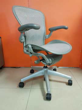 A platinum Herman MIller Aeron Titanium chair tilted to the right by 45 degrees in front of two industrial orange storage doors.