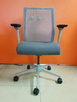 A grey Steelcase Think Chair with black armrests, a mesh back, and padded seat positioned in front of an orange wall.