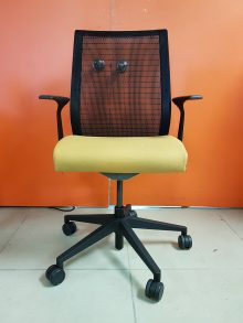 A Steelcase Think Chair with a yellow seating pad, black armrests, and a black mesh back sitting in front of an orange wall.