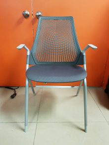 A greay Herman Miller Sayl stacking chair with arm rests and a mesh back, facing straight toward the camera in front of two orange industrial double doors.