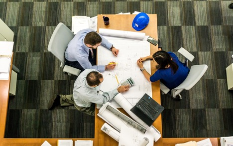 Overhead view of two men and a woman sitting at an office workspace
